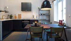 #reforma #cocina de estilo industrial en vivienda rehabilitada, armarios color carbón con encimera de mármol, frente de azulejo blanco, estantería metálica abierta, suelo de parquet.