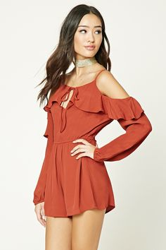 A textured woven romper featuring a self-tie front, a keyhole button back, ruffled trim, long sleeves with an open shoulder, and an elasticized waist.