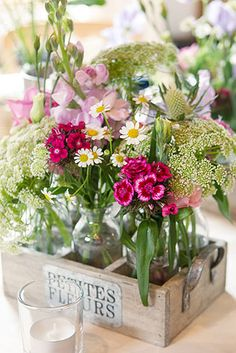 Simple and rustic wildflowers in small apothecary jars put into crate. CP Photography