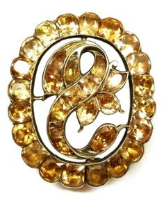 18th century orange topaz oval cluster brooch, Iberian c.1770 , the openwork oval centred by an inverted S scroll with flowerhead and foliate detail, close set in gilded silver  Length 3.5cms / 1 3/8''  Weight: 16g
