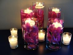 Glass vases with floating candles and submerged orchids...