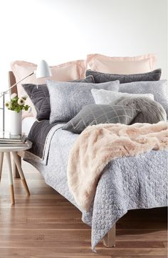 Soft colors paired with a variety of textures create a cozy feel in the bedroom. Especially loving this pastel pink and grey set.