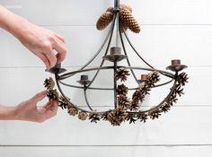 Kiinnitä käpykimput ja -nauhat kynttiläkruunuun kietomalla rautalanganpätkät napakasti rungon ympärille. Leikkaa valmiiksi muutamia noin vii...