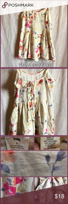 UO Pins + Needles Romper Size 6 Pins and Needles skirted romper, with lace up, corset back and flower detail. The color is difficult to describe- it's a very pale yellow, almost verging on beige (color is well represented in photos). Good used condition. •I'm open to offers on all items!• Urban Outfitters Pants Jumpsuits & Rompers