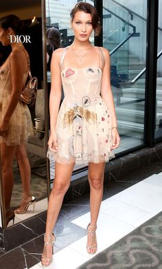 Bella Hadid stunned in a sheer mini Dior dress with whimsical embroidery and flirty tulle. The model kept it sweet and simple with metallic strappy heels and a charming mini backpack. Celebrity Red Carpet, Celebrity Style, Look Fashion, Fashion Show, Fashion Clothes, Isabella Hadid, Bella Gigi Hadid, Dior Dress, Vogue