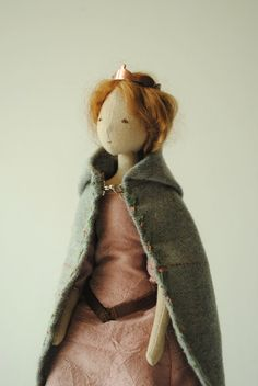1 of 3 A small cloth doll designed and handmade in Australia from discarded and vintage materials.Awoodland queen wearing a little copper crown (hand-made for me in Scotland by Maike Browning Jewelery).Made from cotton remnants,she wears a hand-stitched, dusky pink silk dresswith atiny leather belt, and a pale-blue woollen hooded cloak with hand embroidered trim.This is a completely one of a kind, uniquedoll, handmadefrom carefully salvaged fabric remnants and worn-outantique clot...