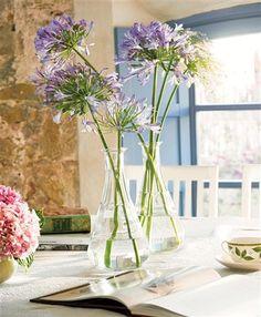flores lilas en botellas de cristal