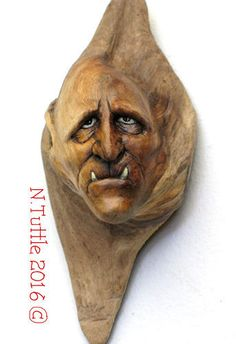 """""""Lost in Misery""""     4½ inches tall and 2 inches across his widest point.  This little demon is carved into an uncommon Alder knot.  I've added a bit of white paint to the teeth and eyes to   help them stand out from the naturally dark wood.  Signed and dated:   N. Tuttle 3/25/16"""