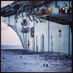 Sailors aboard the amphibious assault ship USS Peleliu jump off the ship's lowered port-side aircraft elevator during a command swim call. Where would you want to have a swim call? #AmericasNavy #USNavy #Navy navy.com
