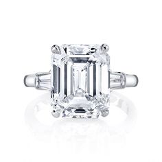 HALLE is a three stones setting, custom engagement ring by Jean Dousset - jeandousset.com - pictured in Platinum with an Emerald cut diamond and 2 step-cut trapezoids.#EmeraldCut #EmeraldDiamond #Engagement #Ring #DreamRing #EngagementRing #Platinum #threestonesetting #DiamondRing