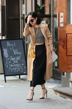 How to wear a midi skirt if you're short: Vanessa Hudgens in a black skirt, crop top, ankle-strap heels, and camel coat