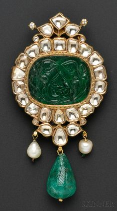 Fine Antique Carved Emerald and Diamond Pendant, India, probably 19th century, set with a carved emerald tablet depicting flowers, foliage, and Islamic script, measuring approx. 31.00 x 21.44 mm, framed by rose-cut diamonds, and suspending a carved emerald drop measuring approx. 29.00 x 15.90 mm, flanked by pearls, high-karat gold mount with reverse pierced and finely enameled, 3 7/8 x 2 in.