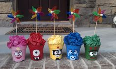 Hand painted plastic flower pots filled with tissue paper and windmills