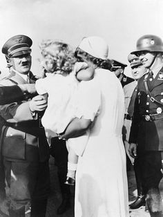 Adolf Hitler and Heinrich Himmler with a mother and her child.