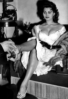 Sophia Loren tries on shoes.