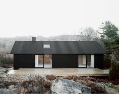 a renovated 1950s cottage sheathed in black pine tar-coated plywood near Gothenburg, Sweden by Johannes Norlander Arkitektur