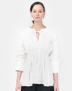 La Chemise Arlesienne in Off White by Jacquemus. This linen and cotton blend button up shirt features a rounded collar at boatneck with tie closure, a fitted waist, vertical pleating at seamed bib, six pearl white button closures at placket extending from midline, a gathered seam detail at inner seam and a keyhole opening at back neck with tie closure.  50% Cotton 50% Linen  Made in Bulgaria  Dry Clean  $485