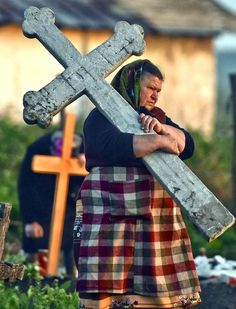 A woman carries a stone cross in a cemetery in the village of Copaciu, southern Romania, on May 2, 2013.  As part of a Holy Week tradition, Romanians visit, on Maundy Thursday, the graves of their loved ones, light fires and share food with community members in memory of the departed. Orthodox worshipers celebrate Easter on May 5. (Photo by Andreea Alexandru/ Mediafax)