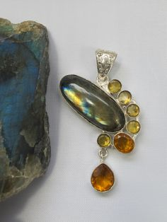 Colors of the sunset! Beautiful Labradorite pendant accented with 7 assorted faceted Fire Citrine gemstones, set in 925-hallmarked sterling silver.