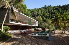 The house, which projects off the mountainside and onto the beach, is located on an island in the city of Paraty (between São Paulo and Rio de Janeiro).