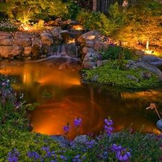Outdoor well lights are installed in the ground and can provide uplight to both structures and landscaping. The well lighting around this pond highlights the plantings and reflects on the water below, casting a charming glow over the entire space.