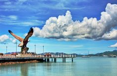 https://flic.kr/p/8CavVP | Langkawi Eagle Pier | Dataran Lang, or 'Eagle Square', is a huge monument in the shape of a sea-eagle in pre-flight pose perched on some rocks. This huge 12-meter high statue greets visitors who come to Kuah by ferry as they ride to the jetty. The eagle is symbolic of Langkawi  Island as its name derives from the Malay word for eagle. The square is a landscaped area with ponds, terraces and bridges, making it a nice place to take a stroll and admire the view of…