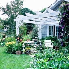 Go with Lush Plantings - Create a botanical-garden experience without acres of space and complicated plantings by concentrating your favorite flowers around the edges of your patio.  -- Lush plantings give it a middle-of-the-garden feel.  -- A vine-covered pergola adds protection from the weather.  -- Simple flagstones add an irregular edge and blend the patio into the yard.