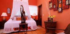 Canopy bed and carved giraffes with coral walls