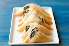 Spanakopita is delicious, easy, and a great appetizer for a crowd. These spinach triangles are bursting full of feta and onion.