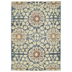 Ornate motifs repeat across this one-of-a-kind rug, a traditional design rendered contemporary through abstraction. Handcrafted in Pakistan from handspun wool, this rug features a cerulean field that contrasts the camel and redwood patterned overlay.