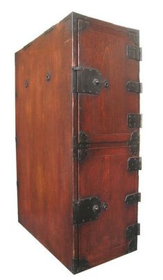 Antique Japanese tall gyosho bako (merchant's box), made of sugi (cryptomeria) wood, top door opens to 6 small interior drawers and bottom door opens to 4 small interior drawers, all drawers of different sizes, iron hardware with locks and unusual hooks, chrysanthemum shaped hardware in corners, rings on sides for tying ropes as this piece would have originally been made to be carried. Edo Period (late 18th/early 19th century).