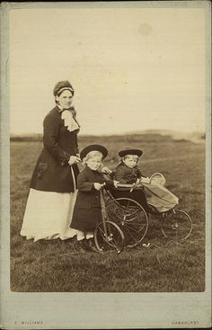 Outdoor portrait of nanny pushing a baby in a pram and with a young child with a bicycle. Kent, 1890-1900.