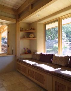 Love the big windows and seats. And the beam work of course. Interior of straw bale house