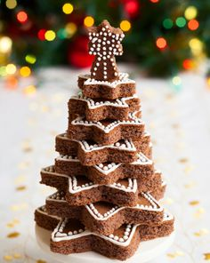 Réalisez plusieurs gâteaux au chocolat puis découpez-y des étoiles de tailles différentes. Décorez de glaçage royal (mélange de sucre glace et de quelques gouttes d'eau) à l'aide d'un cône en papier cuisson. Disposez-les les unes au-dessus des autres.