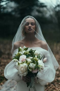 white dress and flowers, and yet so dark and moody. Very couture with the giant sleeves.