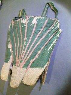 Rare corset ou corps à baleine, époque Louis XV. Canevas de chanvre recouvert de carton et de toile grossière. Extérieur recouvert de fin taffetas Florence vert, baleinage souligné par de minces rubans de soie rose vif appliqués en rayons. La pièce d'estomac est en forme avec godet d'aisance pour la poitrine (poche à herbes parfumées?). Large baleine latérale de maintien en acier, bretelles en soie. Hauteur du dos avec oeillets de laçage: 40 cm; devant: 30 cm (usures et frottements exposent…