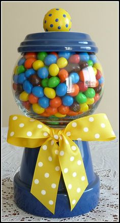 """Here's the gumball machine I made.  It was easy to make with a flower pot, clear glass globe, and grosgrain ribbon; all from Wal-Mart. I use it as a candy dish for peanut M's.  The idea came from a blog called """"A Little Loveliness."""""""