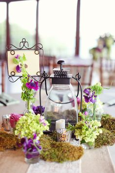 centerpieces: i wouldn't have colored flowers but i like the moss and other cute little things to add