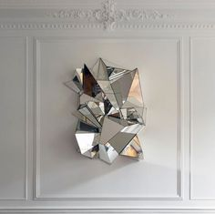 Mathias Kiss' Froisse sculptural wall mirror takes the chic bones of this room to a new level.