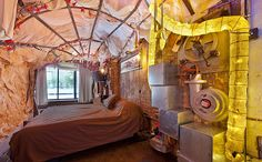"The two bedroom apartment spans 1800 square feet packed with gears, nautical pulleys, parachutes, knobs, horns, chains and other vintage machinery that evokes Jules Verne's ""20,000 Leagues Under the Sea.    Read more: Chelsea Steampunk Apartment is Lit by Repurposed 32-Foot Long Zeppelin LED Lamp Steampunk House – Inhabitat New York City"