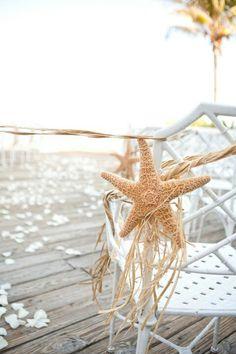 Beach wedding Starfish raffia on each chair decorating the aisle