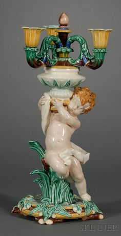 Wedgwood Majolica Figural Candelabra, England, c. 1870, polychrome decorated and modeled with three foliate molded scrolled arms supported by a putti leaning on reeds and tall grass set on a bamboo base.