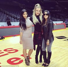 Sister act: Kim with Khloe (center) and Kourtney (right) at Staples Center in LA on Monday...