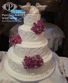 This beautiful standard wholesale package cake has an intricate detailed design. As part of the standard package, you may opt to change the swirl pattern color and have either a white or ivory base color. The bride decorated the cake with fresh flowers that she coordinated with her florist about and completed the look with a couple of birds with music notes as the topper.