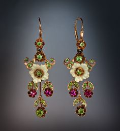 Art Nouveau Vintage Long Earrings These delicate vintage Russian pendant earrings were made in Moscow between 1908 and 1917. Handcrafted in 14K rose gold, decorated with finely enameled pearl white flowers, and set with 44 Uralian demantoids and 4 synthetic rubies.