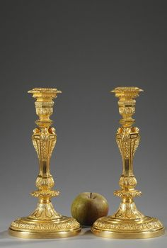 A pair of gilt and chiseled bronze candlesticks in Regency style, the slightly curved barrel decorated with busts, acanthus and floral motives, on a circular foot richly decorated with valan