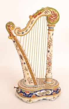 This is a lovely antique French porcelain harp inset with music box by Gabriel Formaintraux from Desvres, circa 1908.  The harp is richly decorated with floral motifs in various colours. Antique Porcelain Formaintraux Music Box c.1908