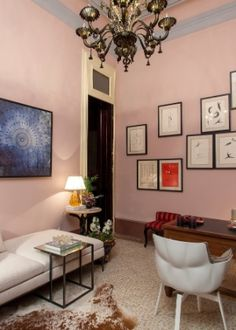 Sala de estar decorada com a chaise de linhas retas e as poltronas giratórias em formas orgânicas. O lustre com acabamento dourado envelhecido e as paredes pintadas em tom rosa pastel trazem romantismo ao ambiente.