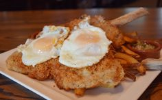 Schnitzel Holstein, crisp herb-breaded veal scaloppini with fried eggs, a lemon, anchovy and caper sauce and hand-cut fries // Green Valley Grill Menu - Greensboro NC