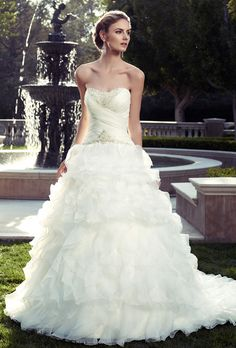 Brides: Casablanca Bridal. Strapless, soft sweetheart neckline with criss-cross pleating on bodice. Crystal, rhinestone, and pearl beaded appliqu�s are on the front neckline and along entire dropped waist seam. Long layers of ruffles create the A-line skirt overlay and gown is finished with crystal buttons along the zipper. This gown features an inside hook and eye fit panel.  moreless
